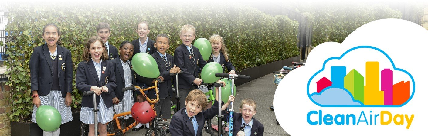 A group of school children with scooters and bikes stand in front of a living green wall
