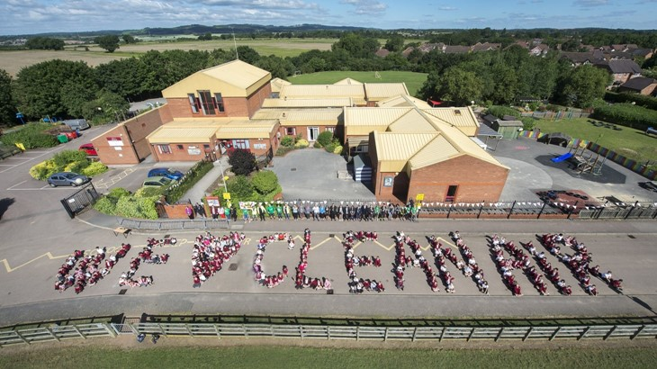A group of school children spelling out the message We Clean Love Air in people on a closed road in front of their school